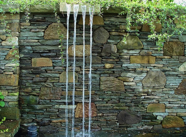 Waterfall from a tall stone wall